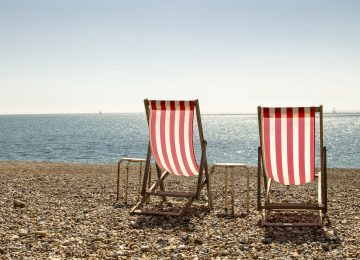 Landscape colour photo of a pair of red and white striped deckchairs on a stoney beach